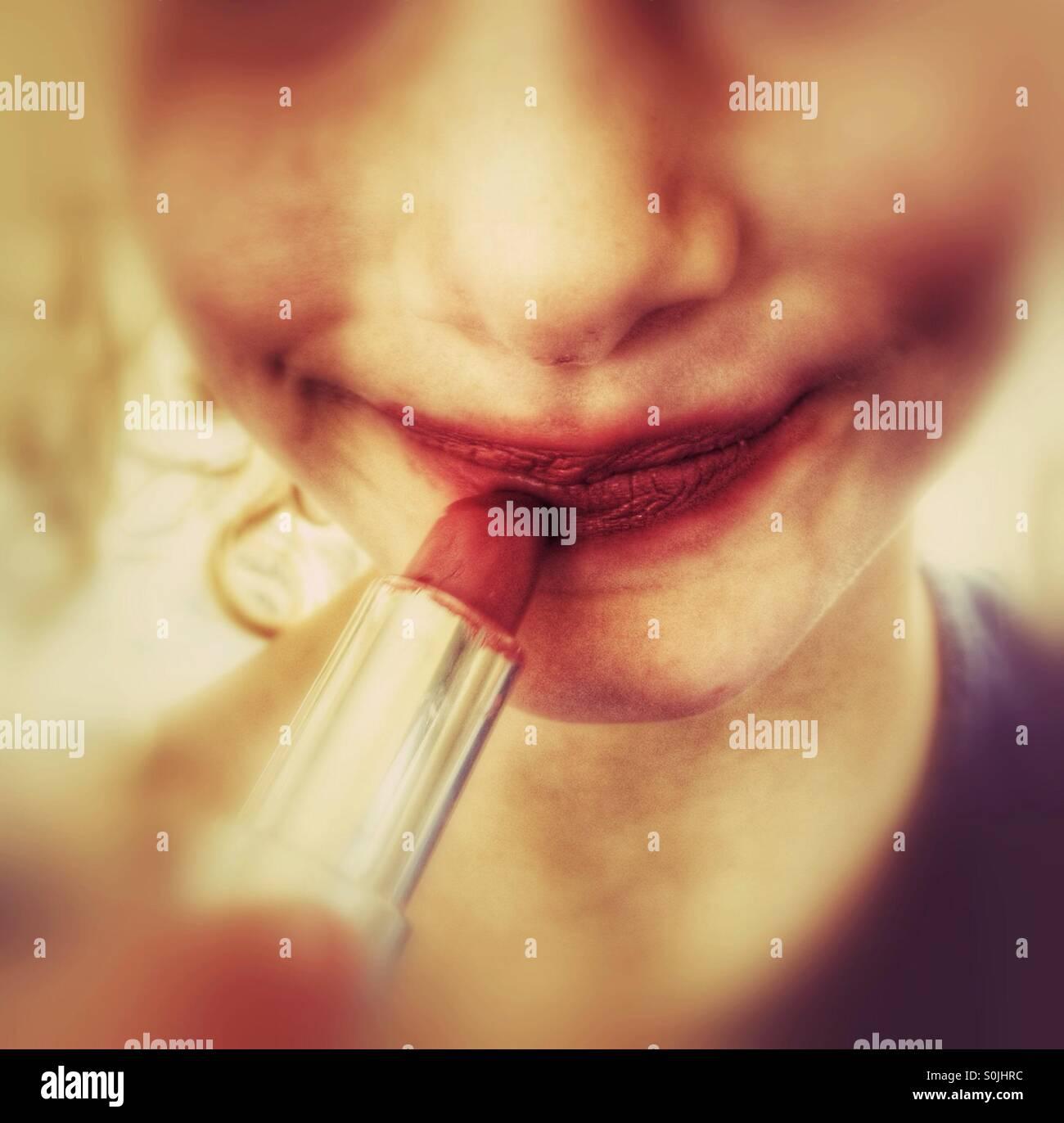 Young girl applying lipstick - Stock Image