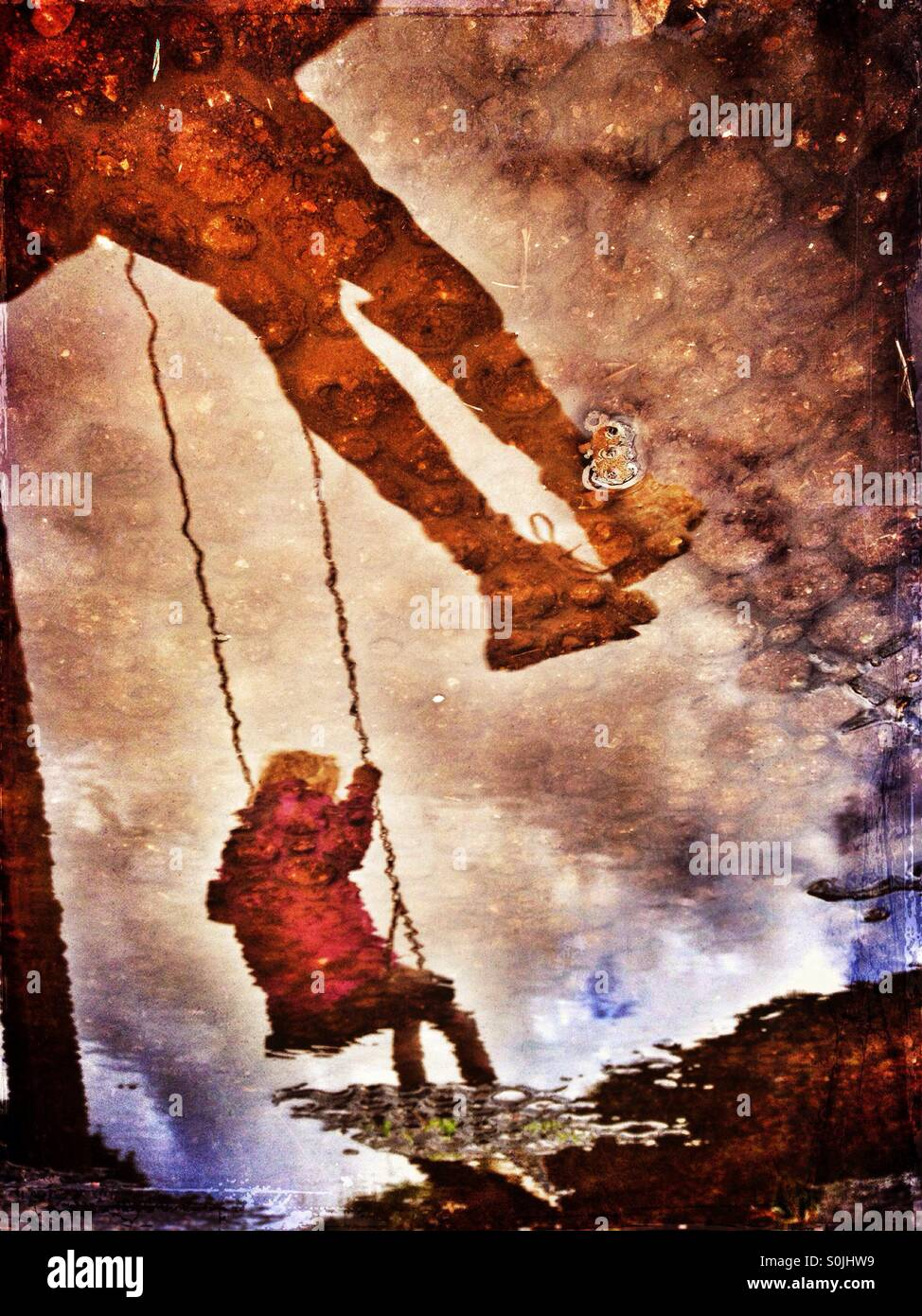 Reflections in muddy puddle of two girls on swings - Stock Image