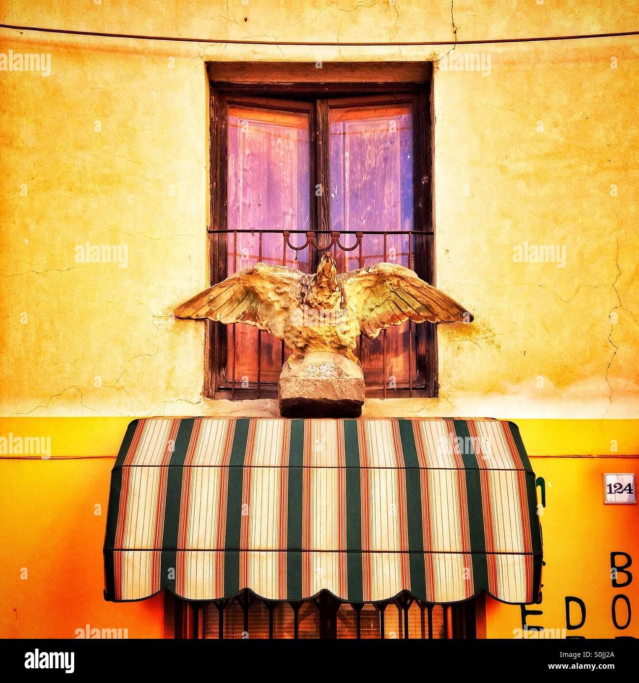 Bird sculpture above awning Borgo a Mozzano Italy - Stock Image
