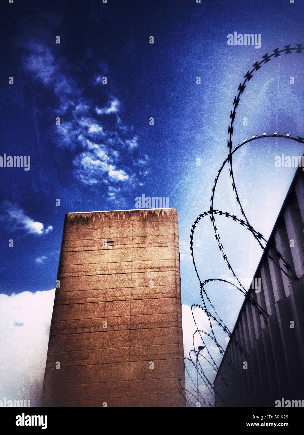 Razor wire fencing and stark building. - Stock Image
