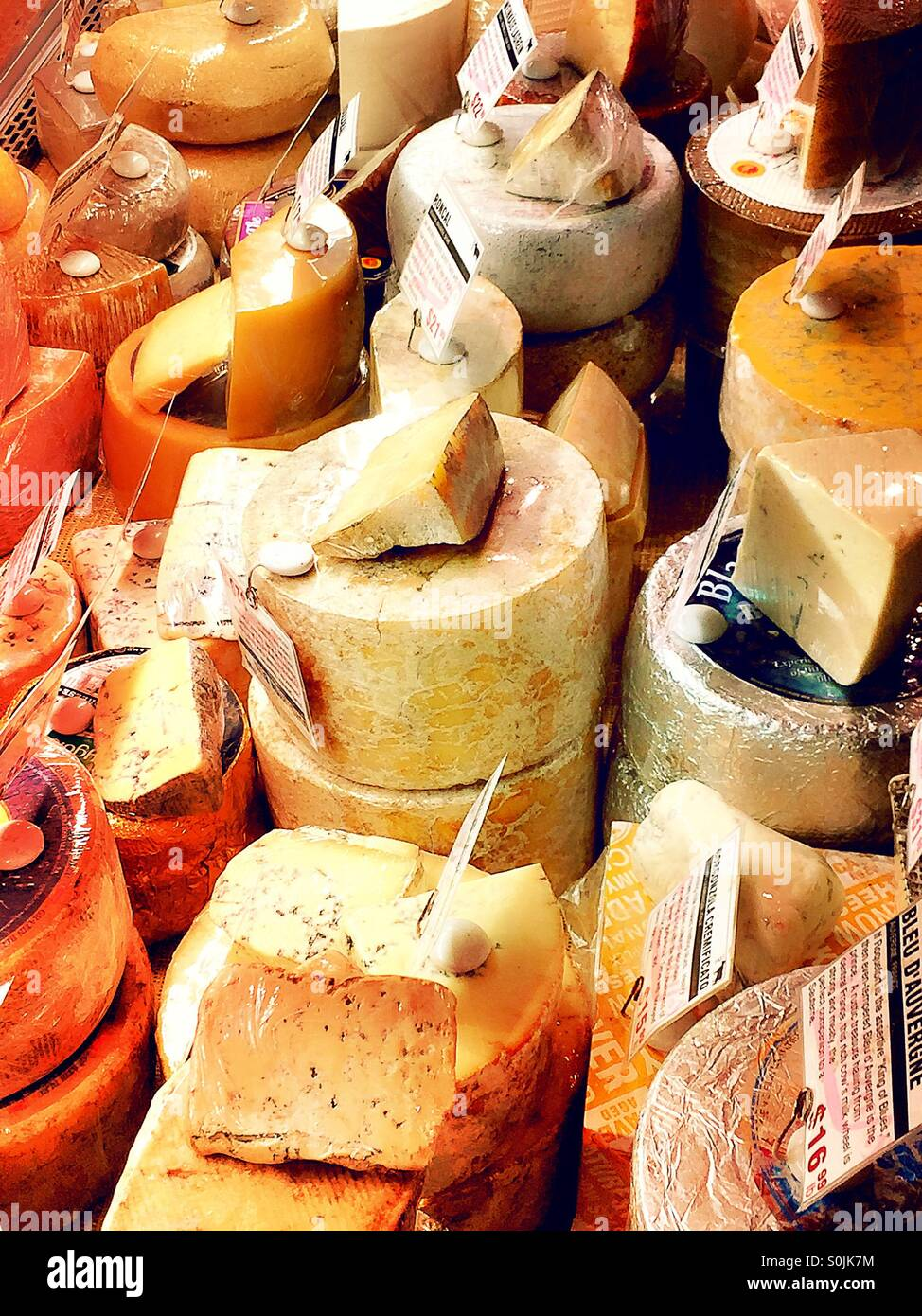 Cheese wheels and slices in a cheese shop display case. - Stock Image