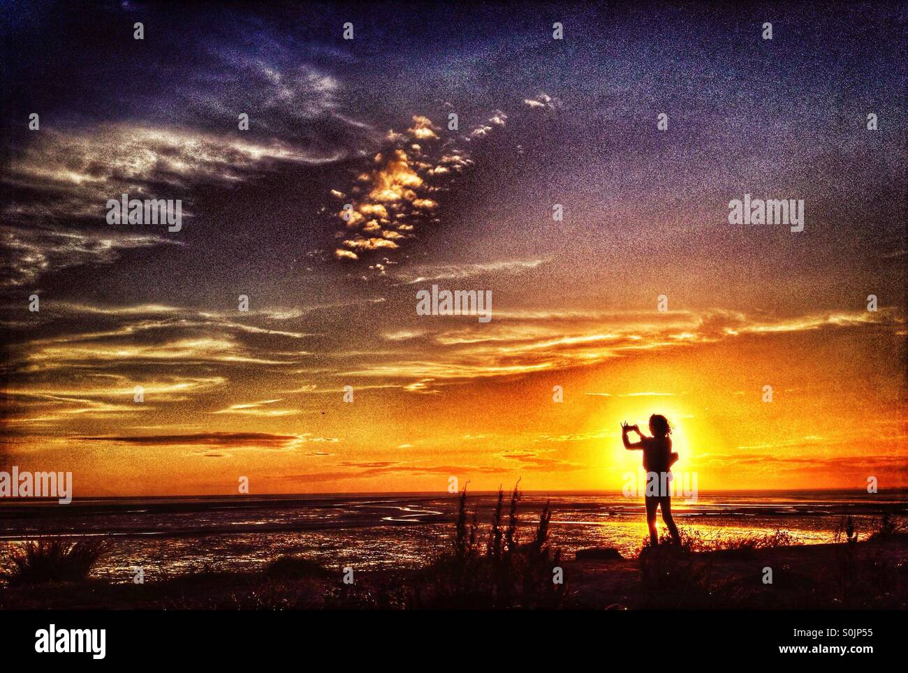 Young girl taking photo silhouetted against the setting sun over Morecambe Bay at Heysham - Stock Image