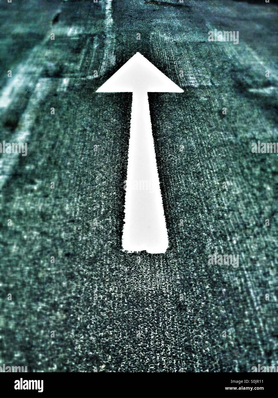 White arrow painted on road - Stock Image