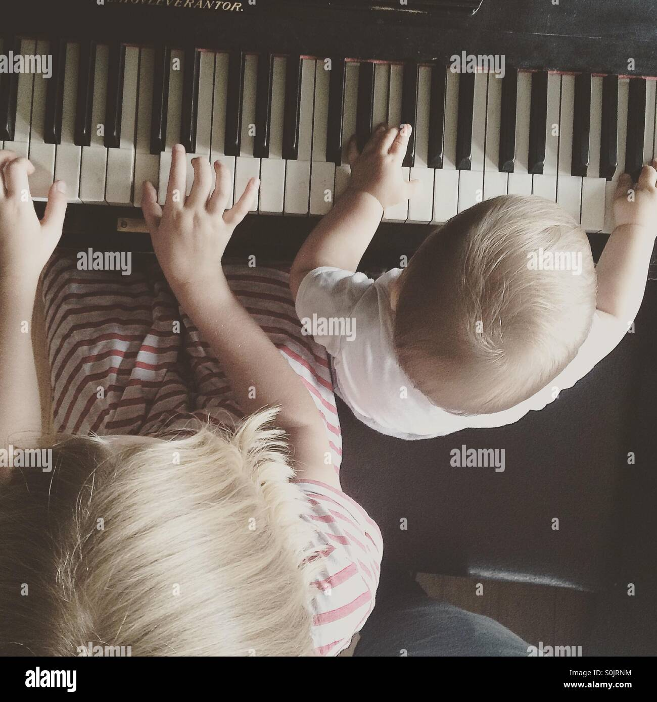 Photo  taken from the top of siblings learning,   playing piano together - Stock Image