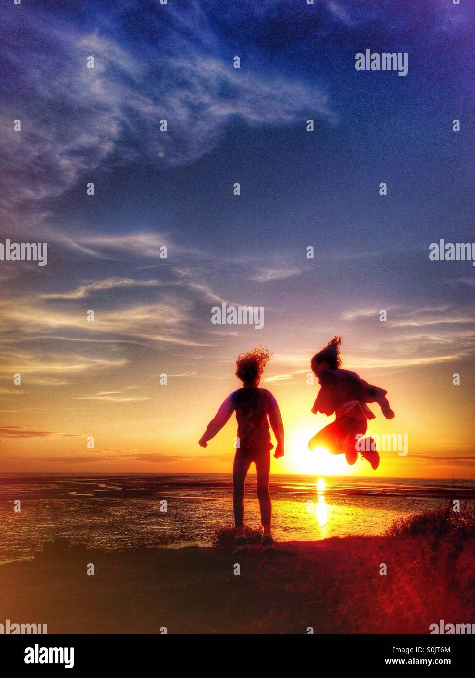 Two young girls having fun jumping in front of the setting sun - Stock Image