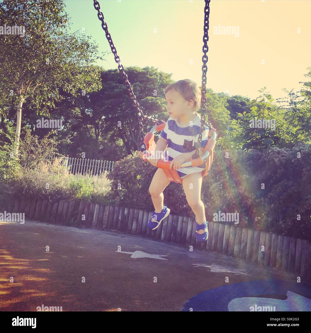 Toddler on swing in park - Stock Image