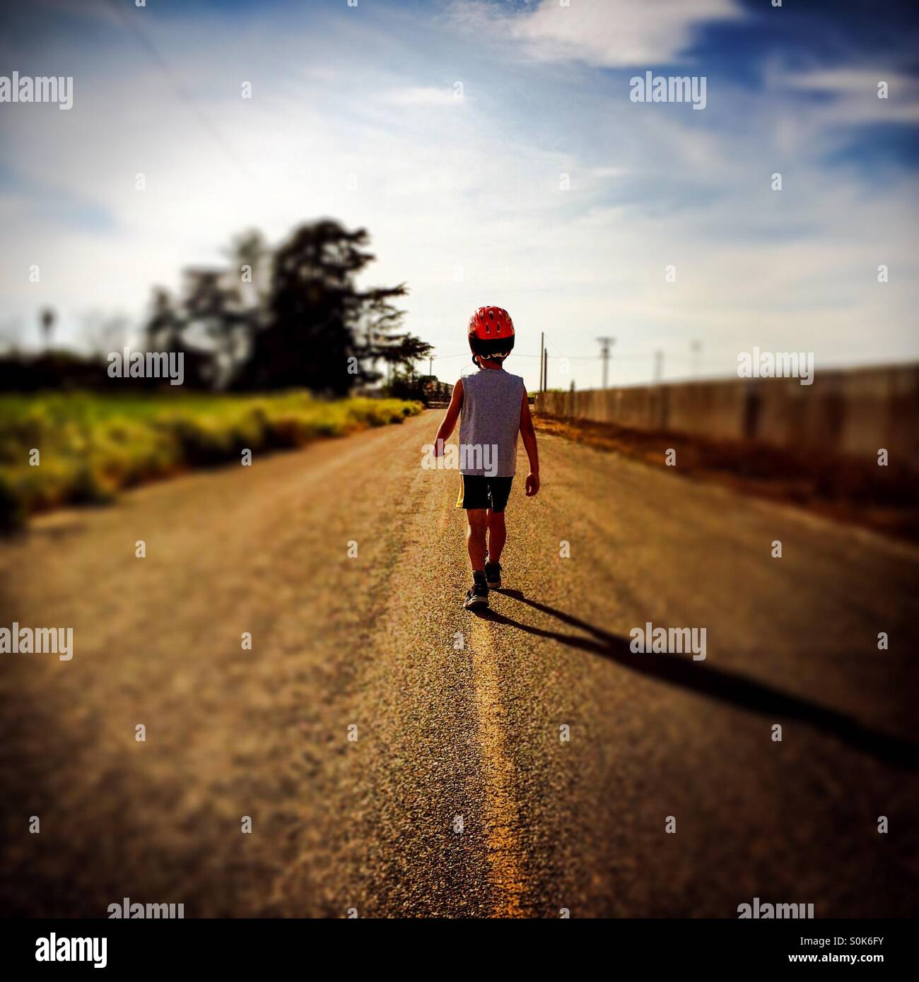 A 7 year old boy walks down the middle of a country road wearing his bicycle helmet. - Stock Image