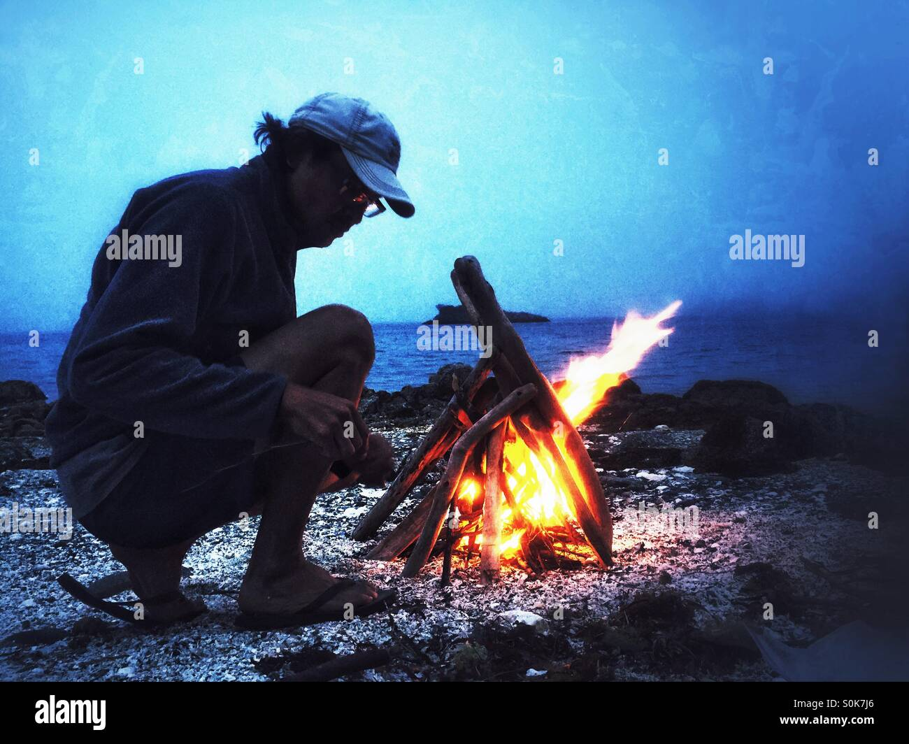 Man building a campfire at twilight on a beach - Stock Image
