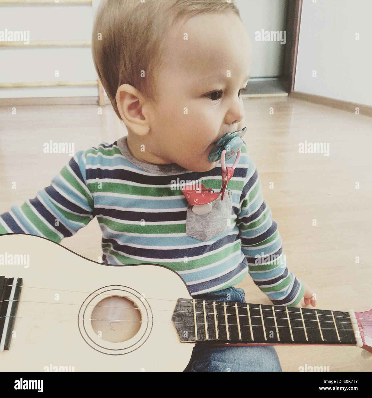 Baby boy playing guitar , looking to the side, sitting on a wooden floor in an empty room, with a pacifier in his - Stock Image