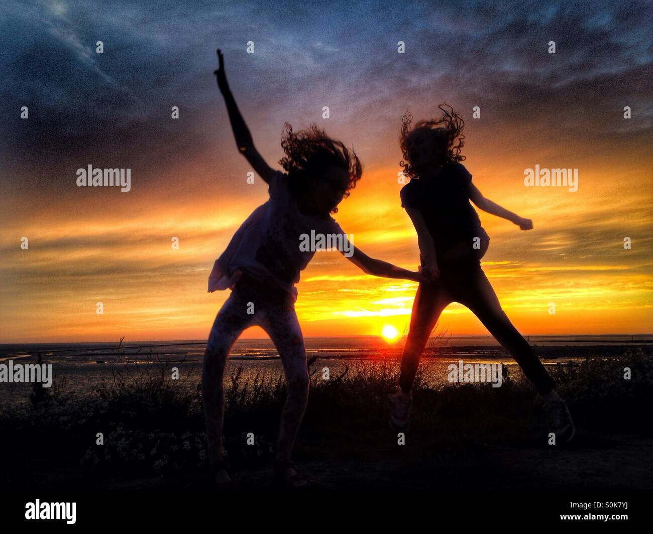 Children having fun in silhouette against the setting sun Stock Photo
