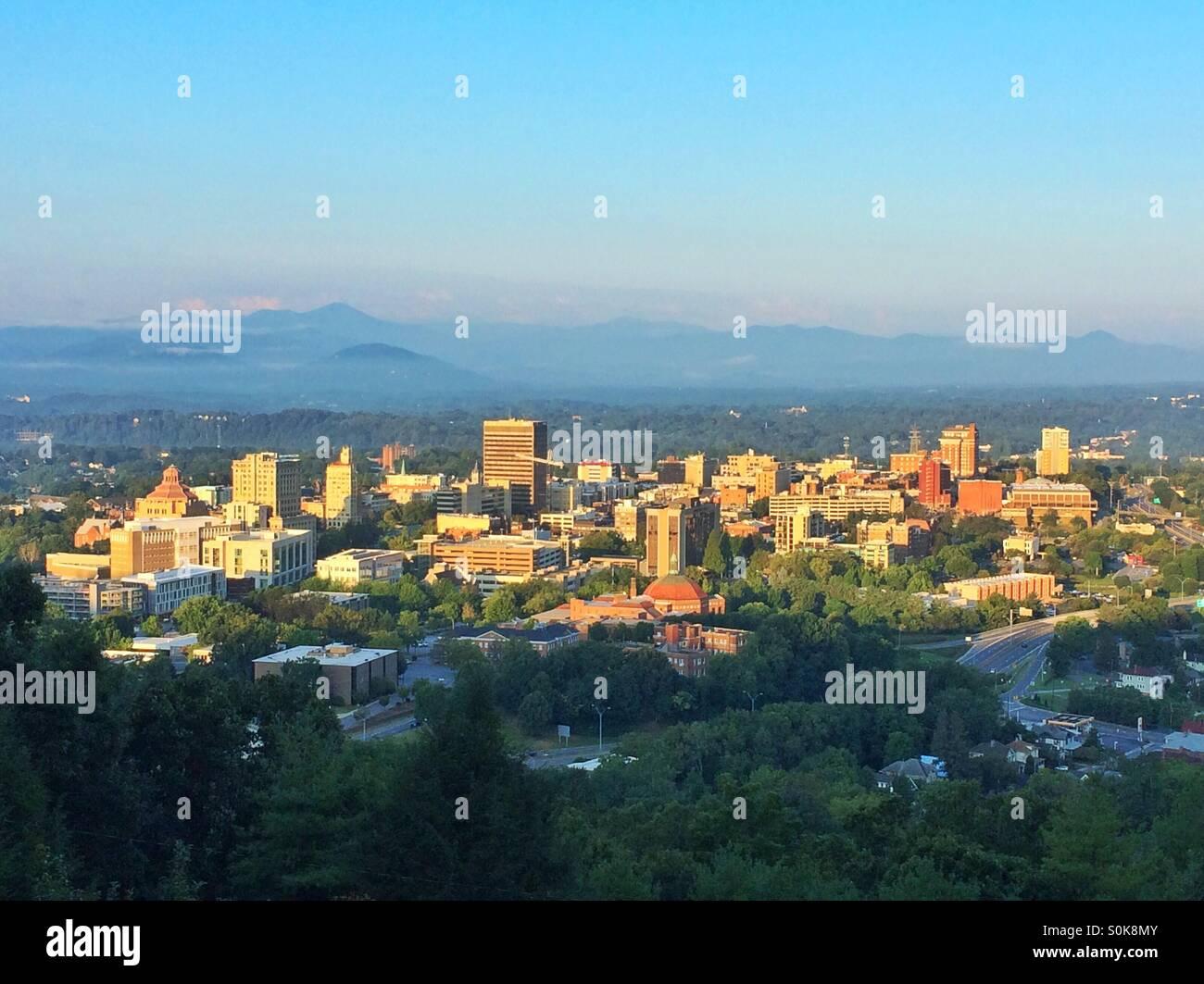 Sunrise illuminates the city of Asheville, North Carolina, nestled in the Blue Ridge Mountains. - Stock Image