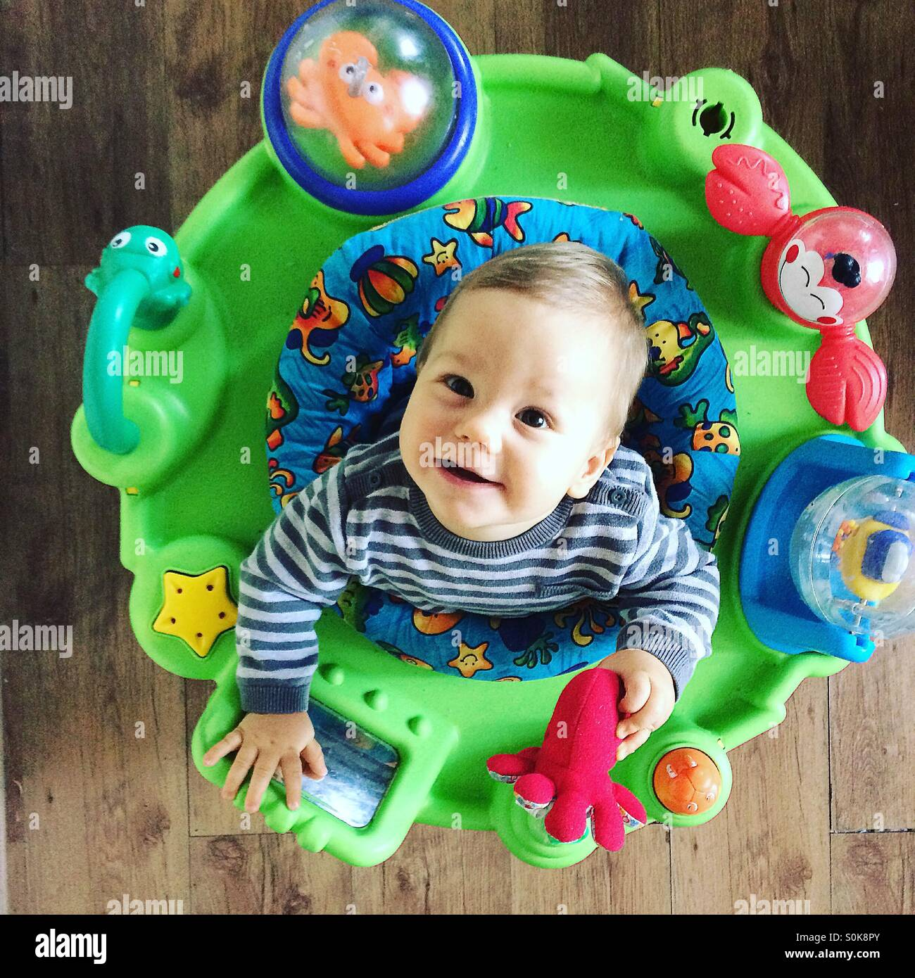 Photo from above  of a smiling 9 months old baby boy , who is sitting in his toy jumpy chair , having a great time, - Stock Image