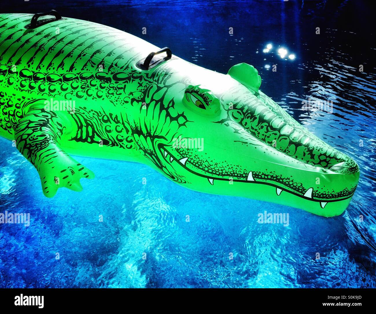 Inflatable Alligator Toy Floating On Blue Water.
