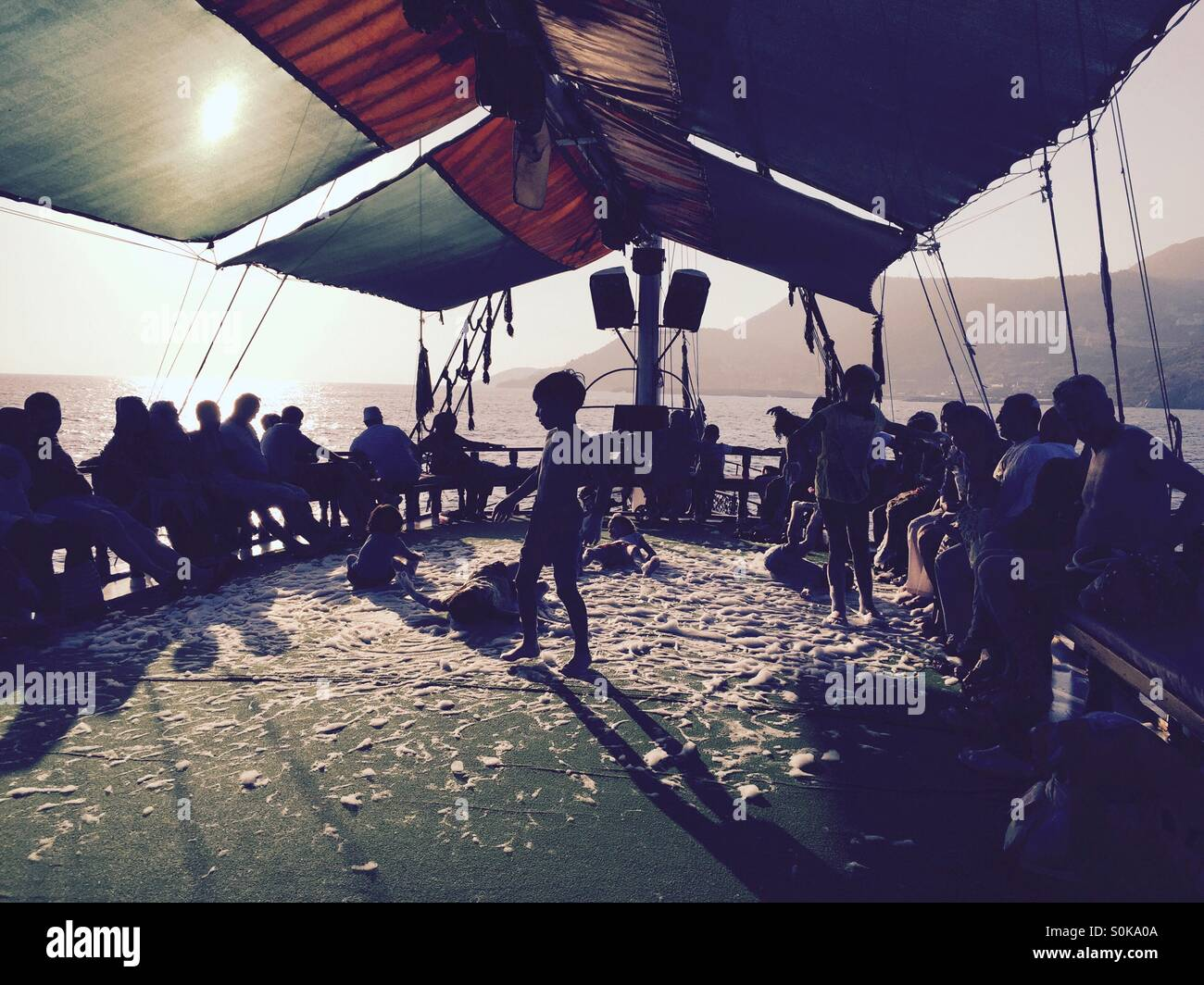 Children enjoying soap party on sailing boat - Stock Image