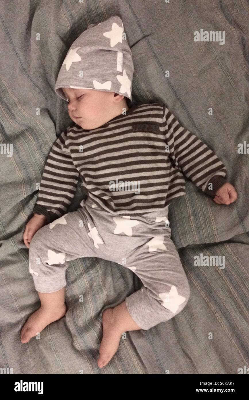 Baby boy dressed in a cute star pants and hat along with stripped sweater , sleeping peacefully on a blanket Stock Photo