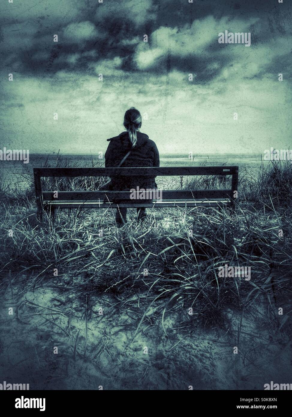 A lone woman sitting on a wooden bench looking out to sea - Stock Image