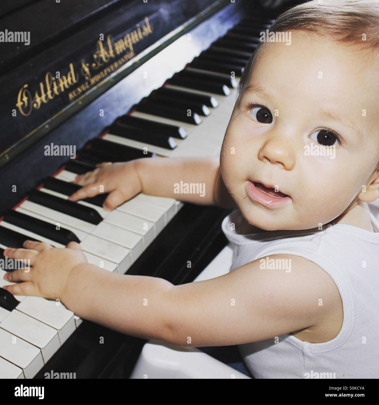 9 months old baby boy playing piano , with both of his hands on the piano keyboard, looking at the camera with a - Stock Image