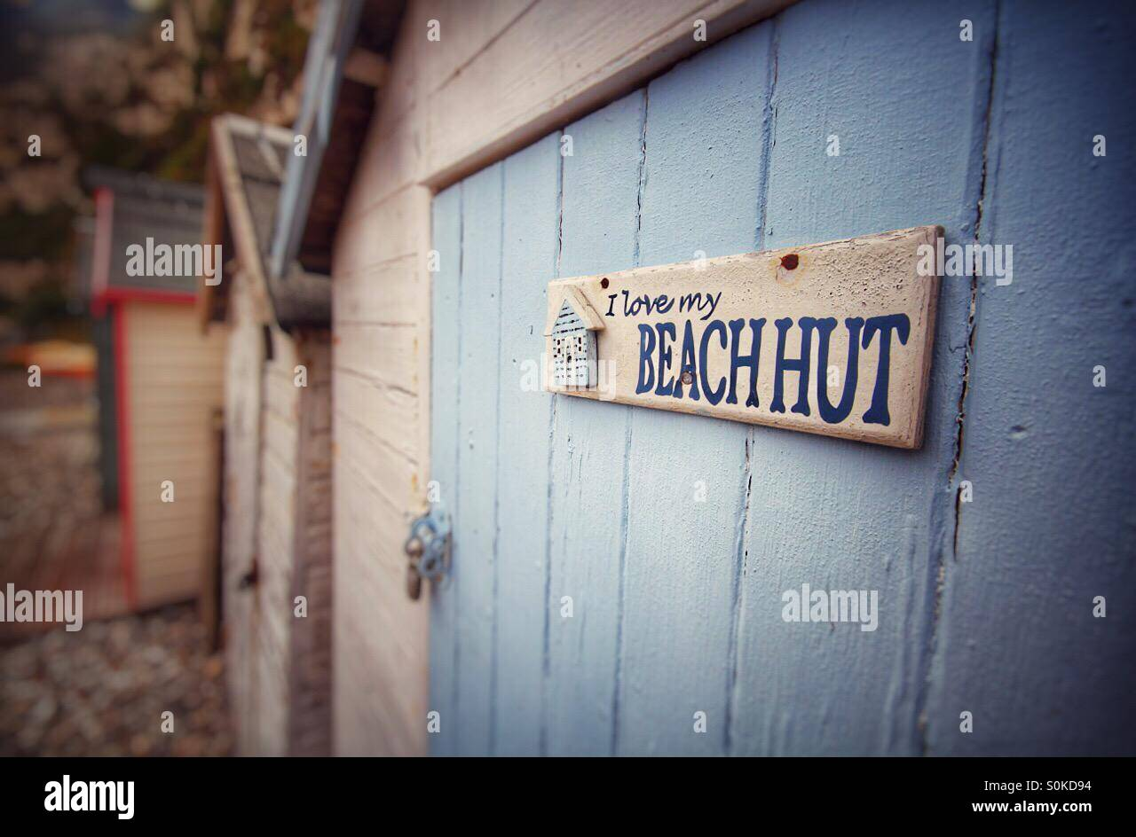 A sign on the door of a beach hut saying I love my beach hut. A row of beach huts on the beach. - Stock Image