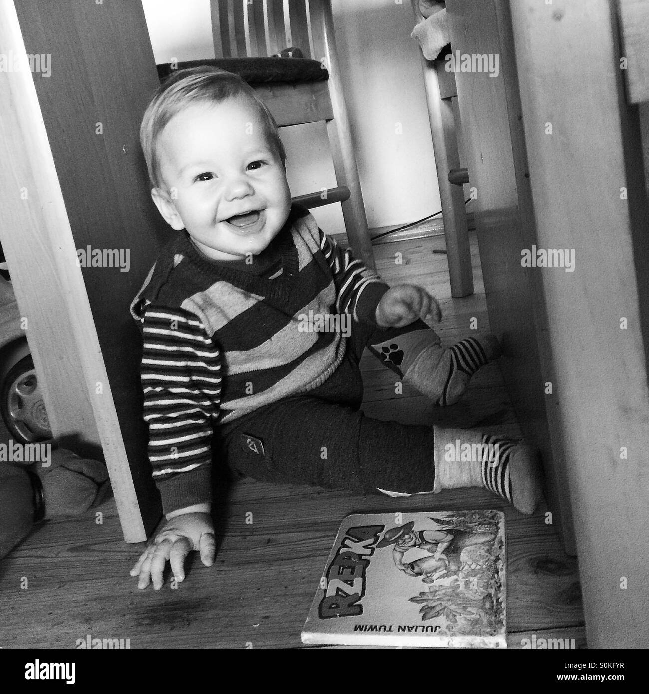Happy  9 months old baby boy sitting underneath the table , playing a game of hide and seek with a hard cover polish - Stock Image