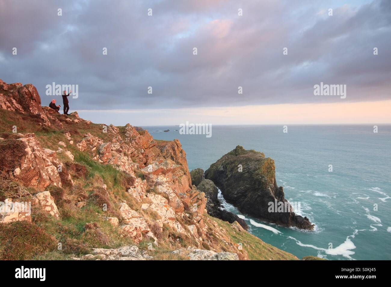 Two people taking selfies on a cliff side at sunset. Overlooking the ocean. - Stock Image