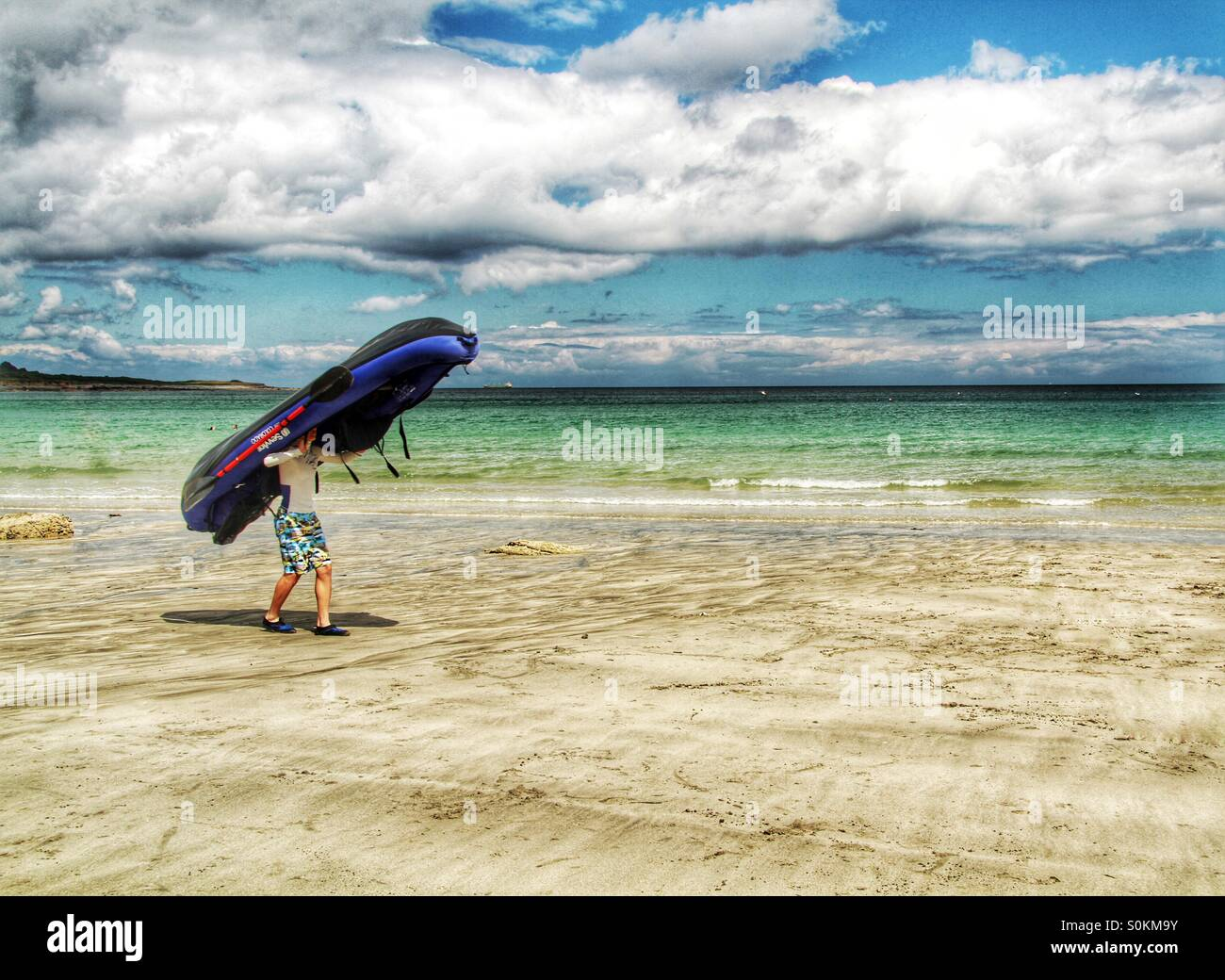 A boy carrying an inflatable dinghy on his head as he is walking along a sandy beach on a summer's day. - Stock Image
