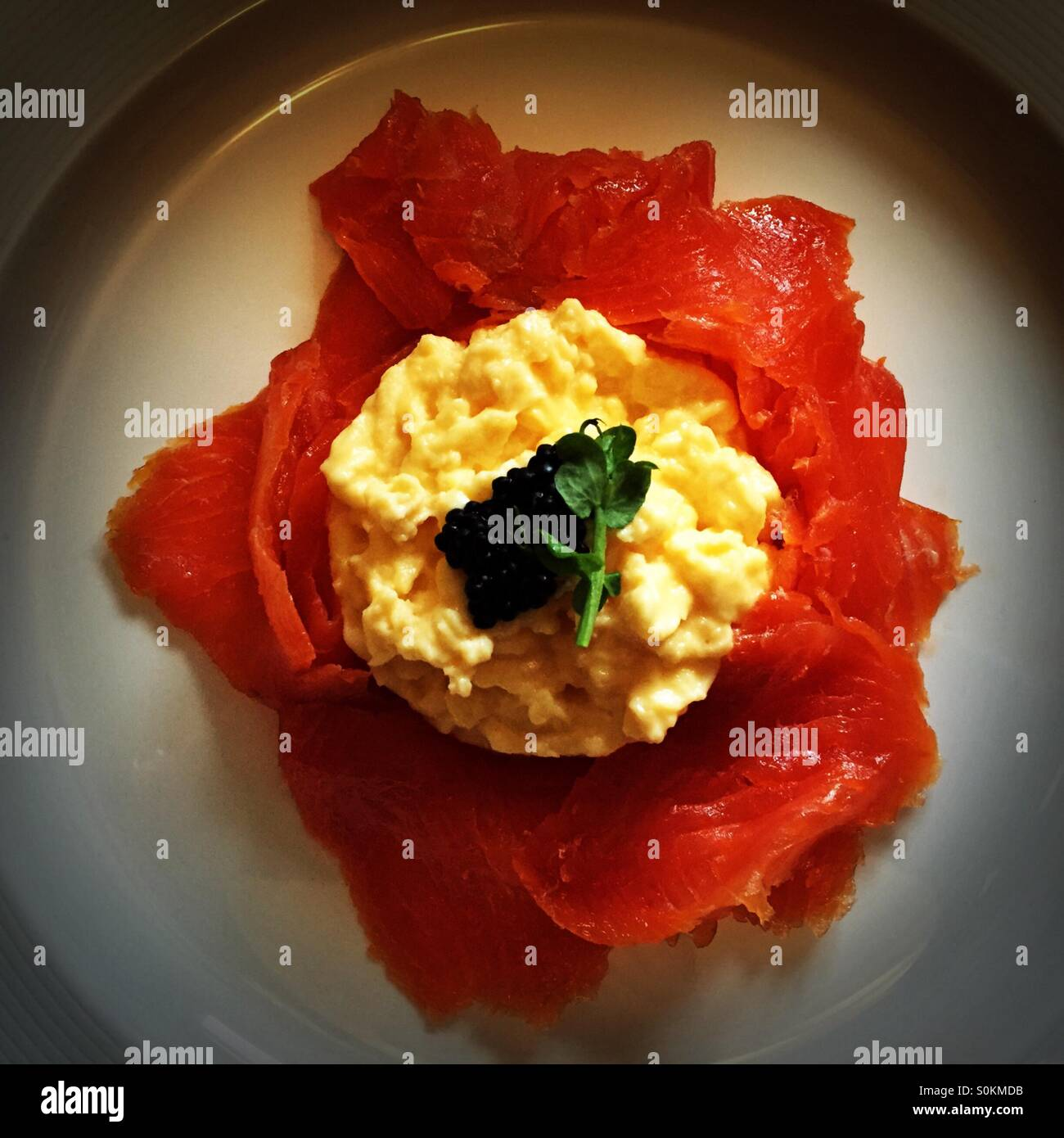 Smoked trout and scrambled egg for breakfast, on a plate. - Stock Image