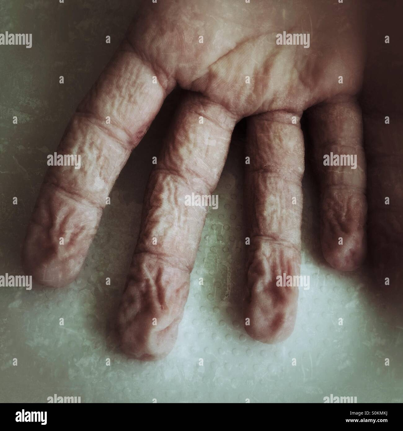 The wrinkled fingers of a young boy after swimming - Stock Image