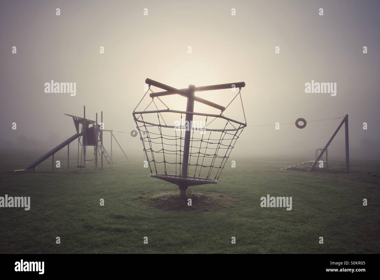 A deserted children's playground on a cold foggy morning. - Stock Image