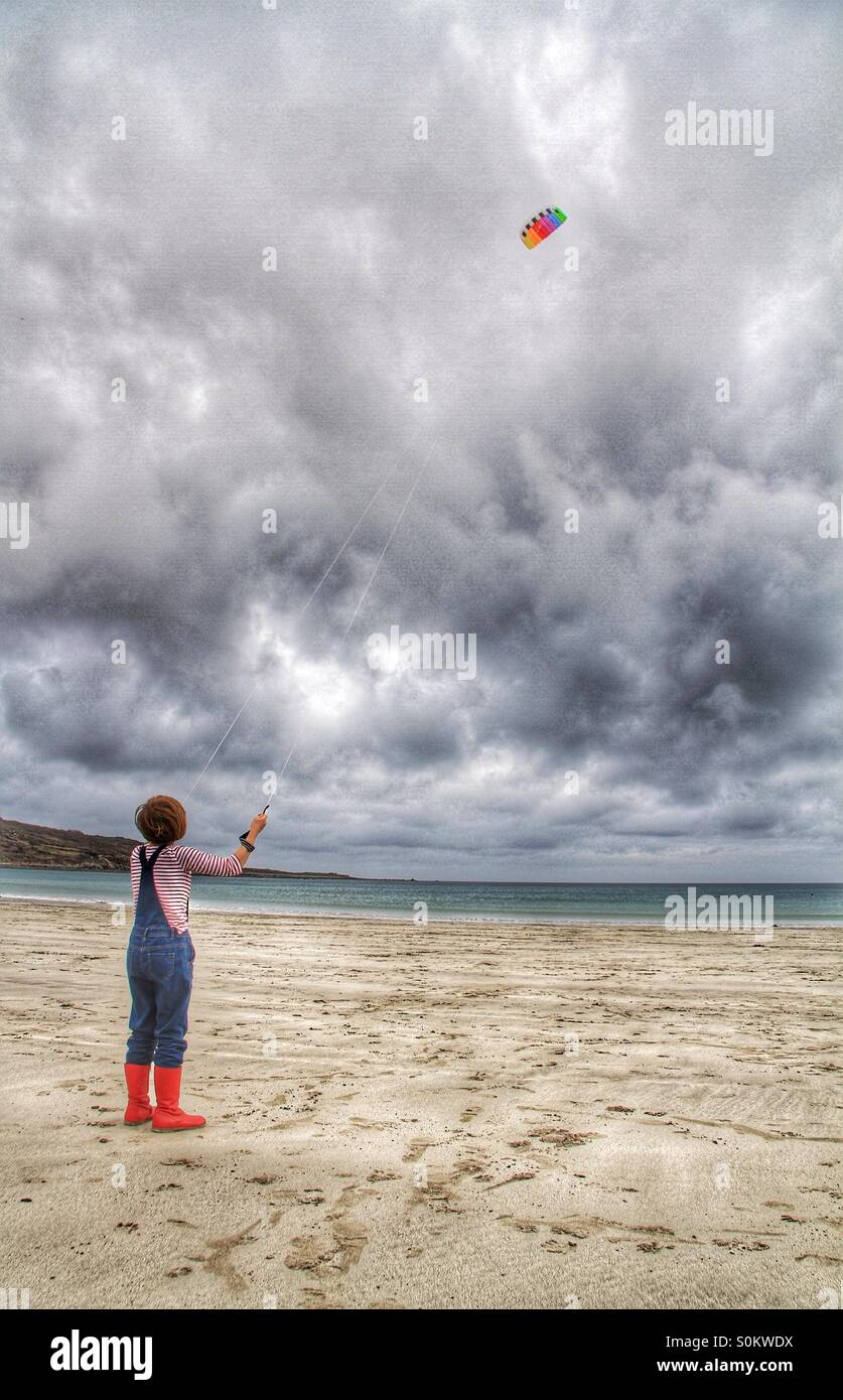 A girl in red wellingtons flying a colourful kite on a deserted sandy beach.  A cloudy stormy sky above. - Stock Image