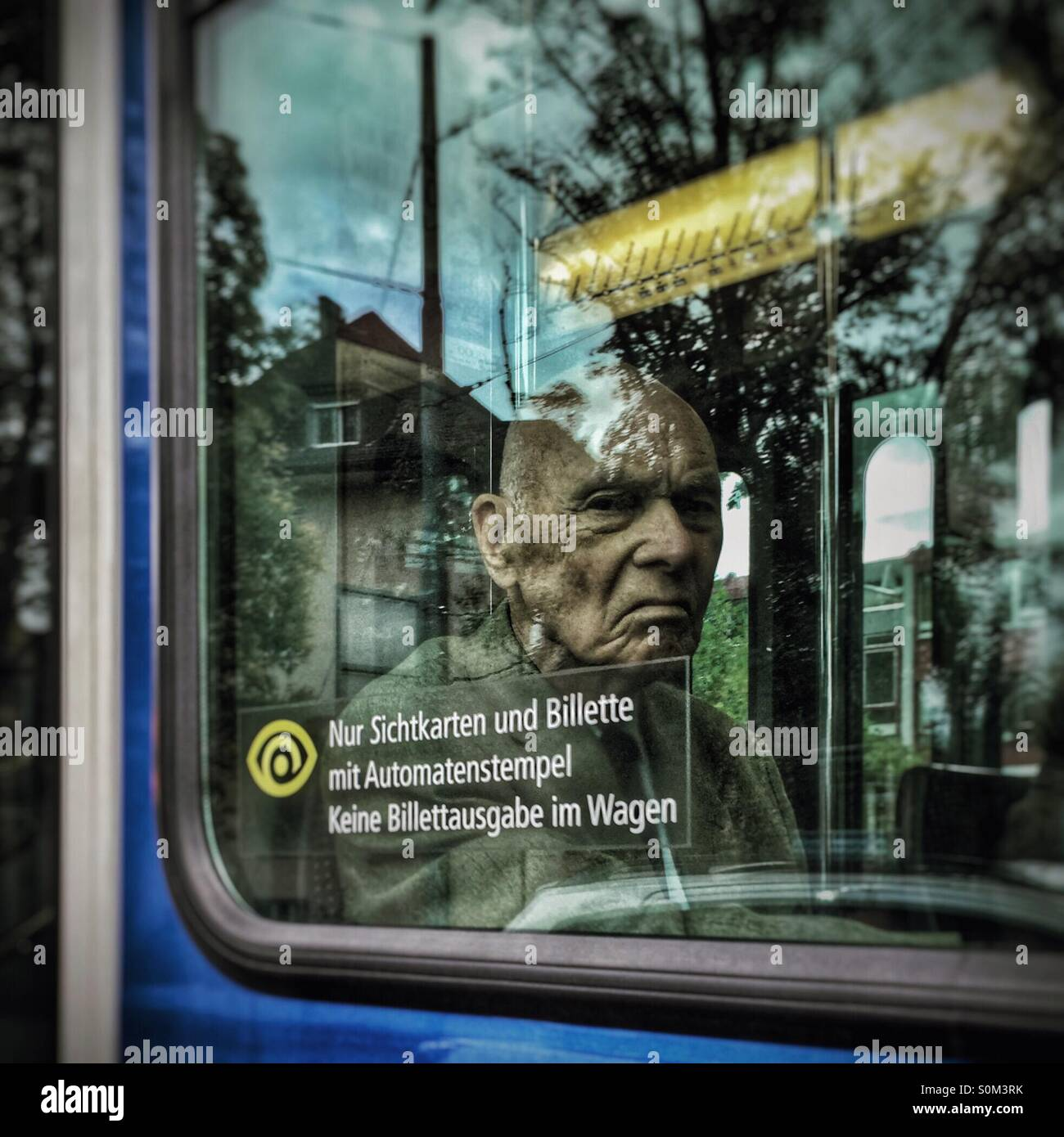 Sour-faced old man scowls through a tram window - Stock Image