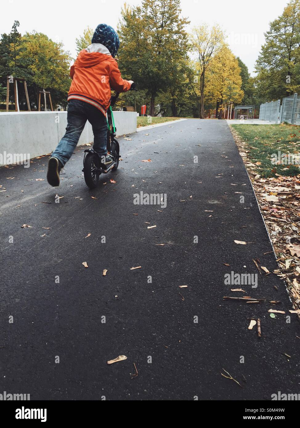 Boy riding a scooter in a park in rainy autumn weather - Stock Image