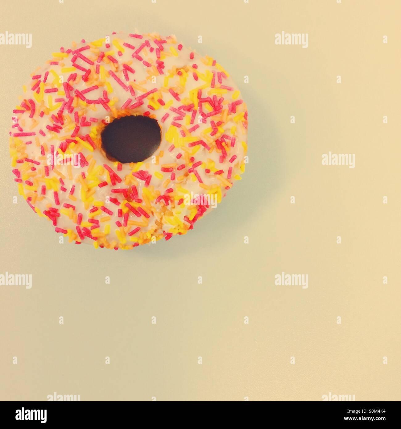 Single ring doughnut with multicoloured sprinkles - Stock Image
