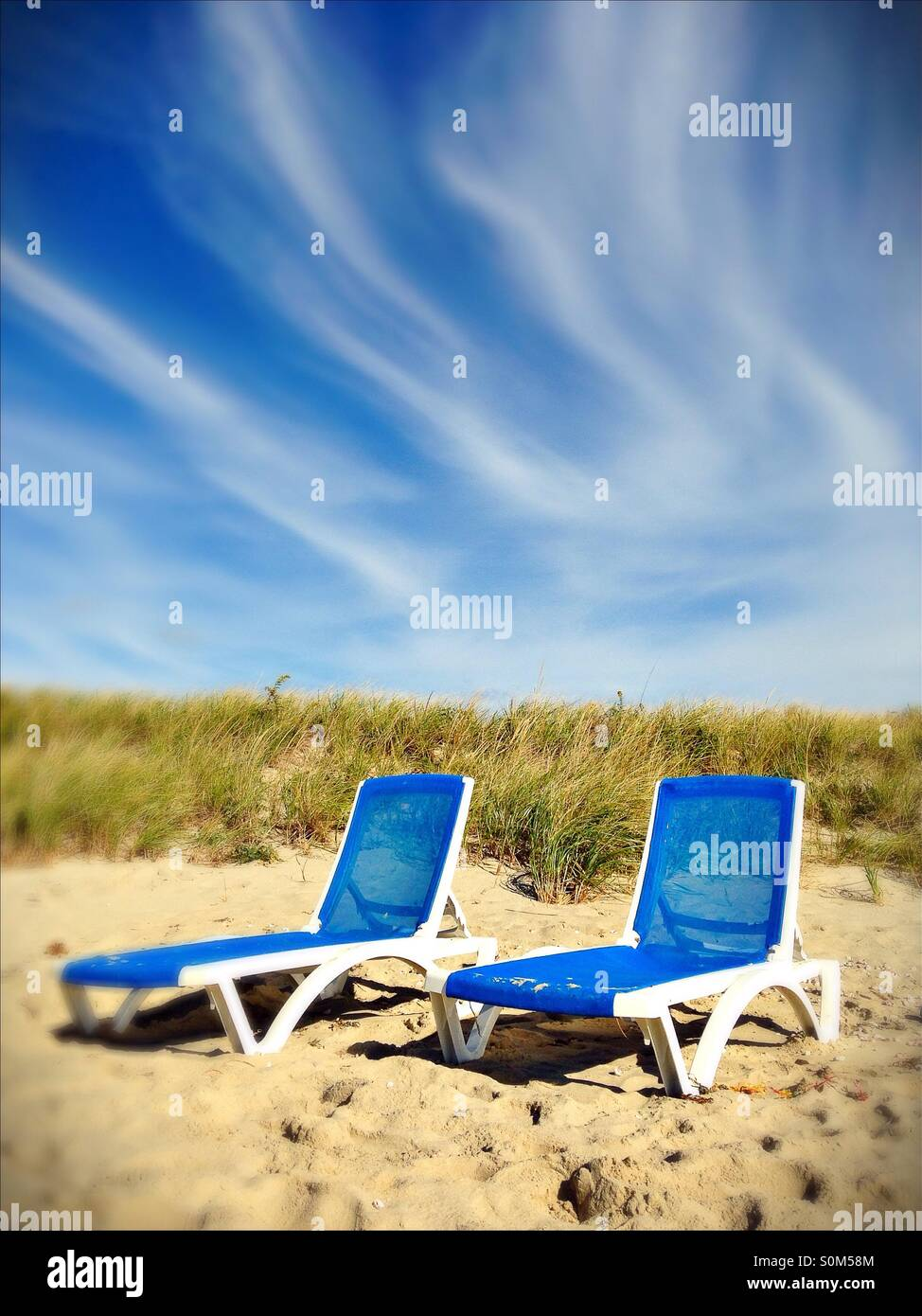 Two blue beach chairs in the dunes. - Stock Image