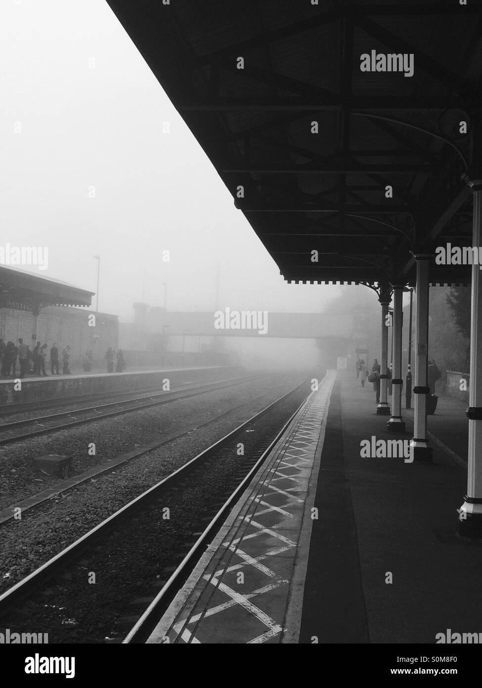 Commuters waiting at Dewsbury train station, West Yorkshire, UK. - Stock Image