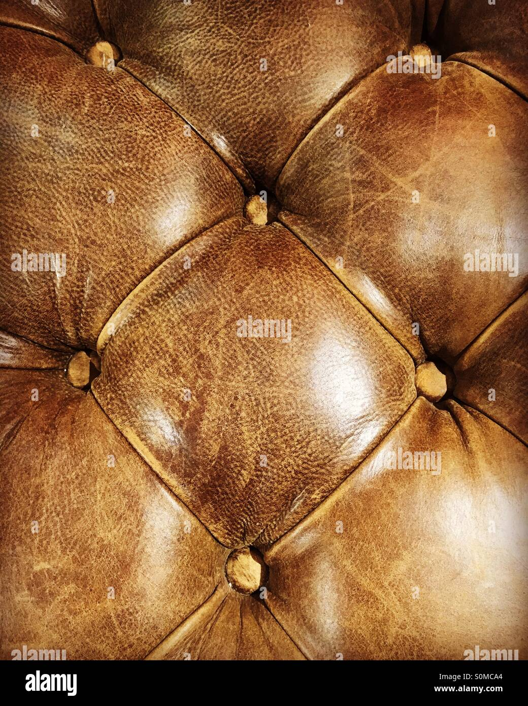 Close-up of a brown, leather Chesterfield seat. - Stock Image