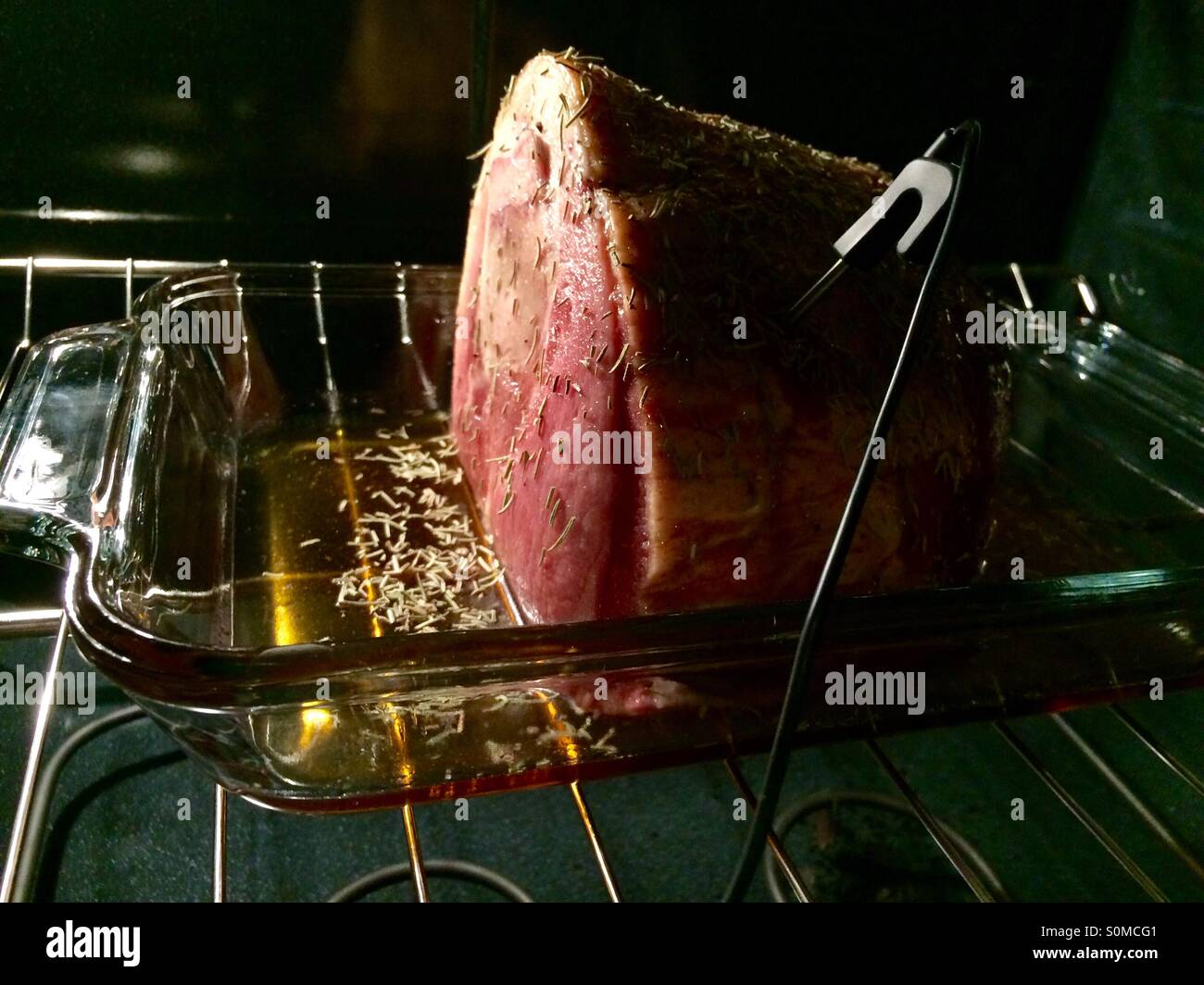 Berkshire ham with maple syrup and rosemary baking in oven with temperature probe - Stock Image