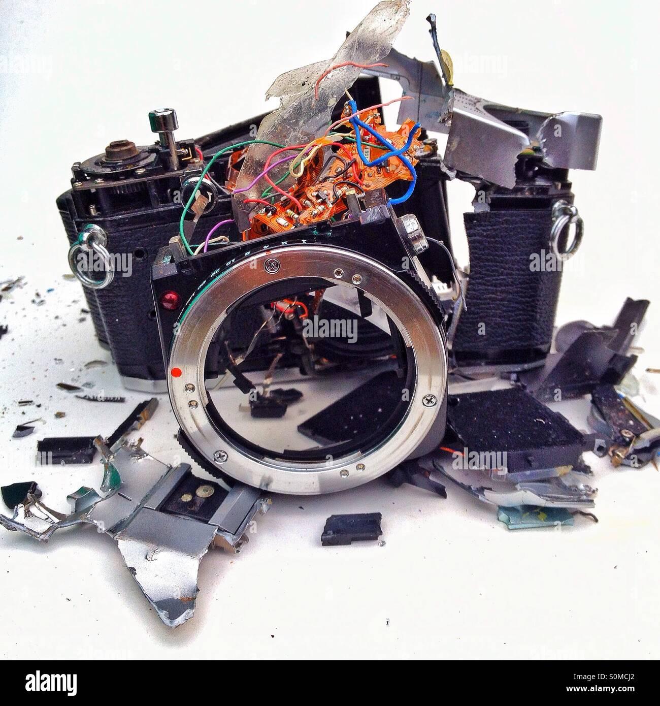 Smashed Olympus SLR film camera - Stock Image