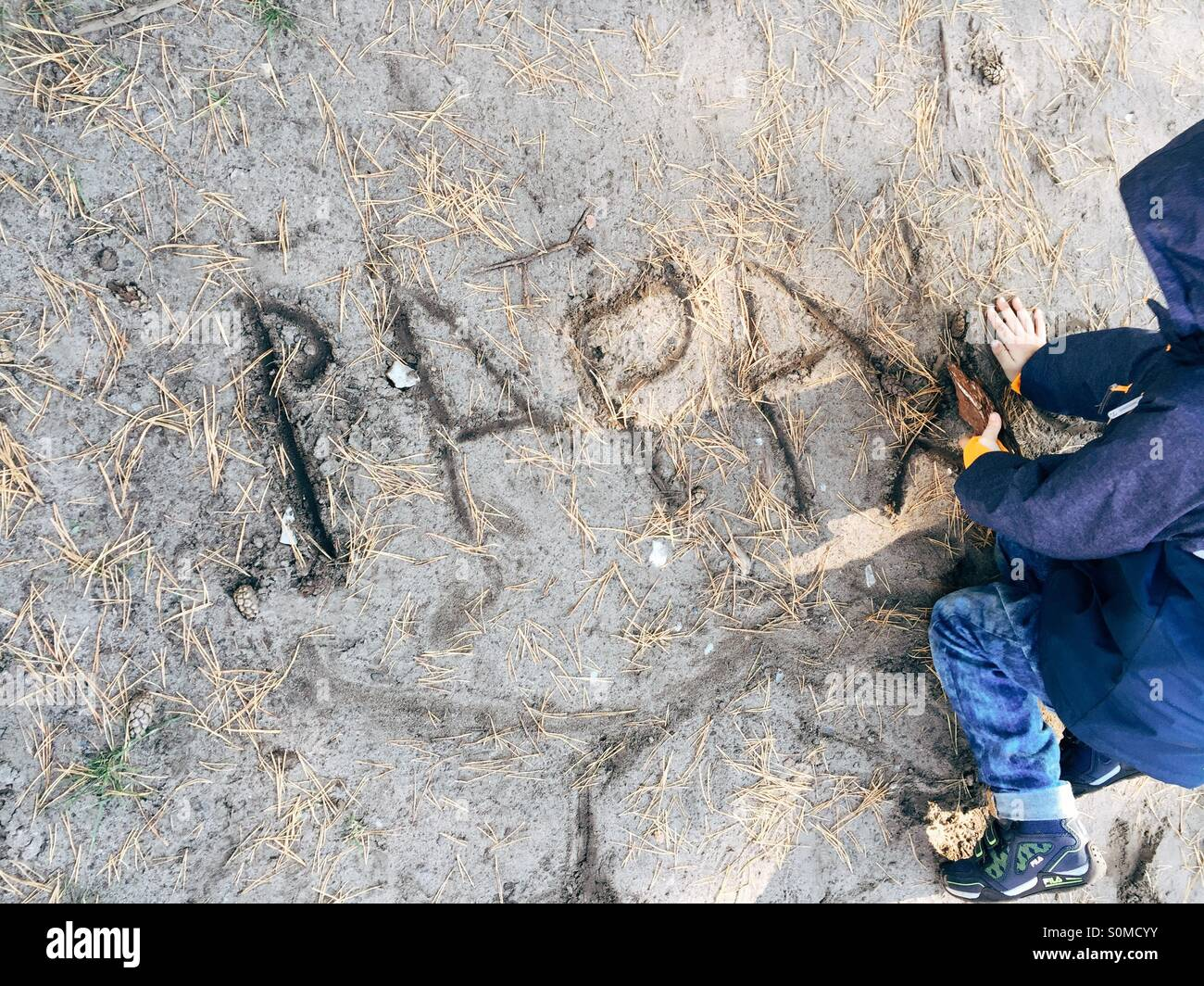 Young boy writing Papa with a stick into the sand - Stock Image