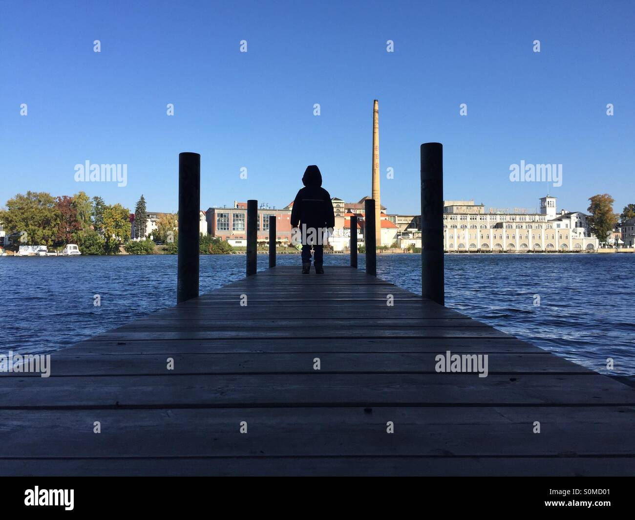 Young boy standing on a jetty Stock Photo