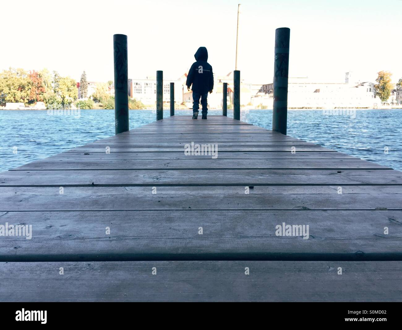 Young boy standing on a jetty - Stock Image
