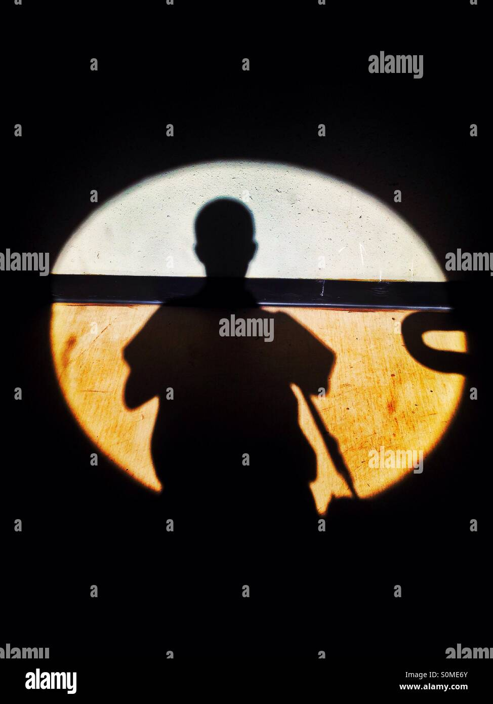 Shadow of a man in a circle of light. - Stock Image