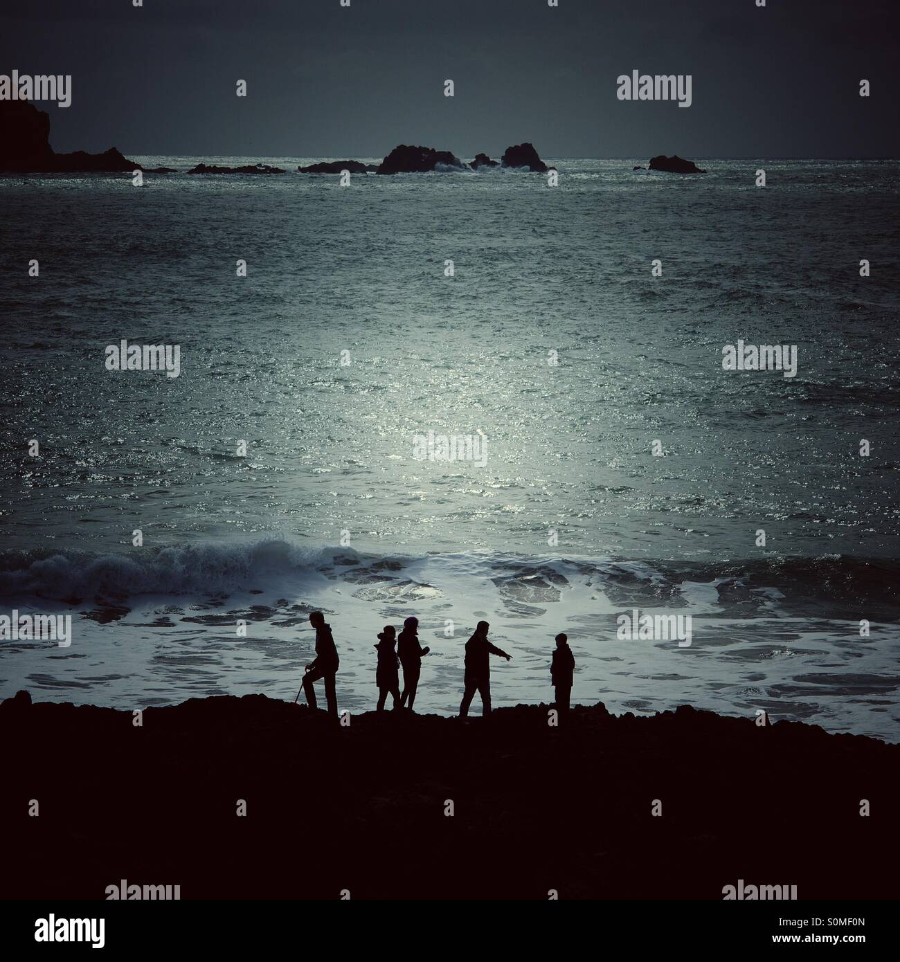 Five silhouettes on an adventure at the seaside. The moonlit Ocean behind them. - Stock Image