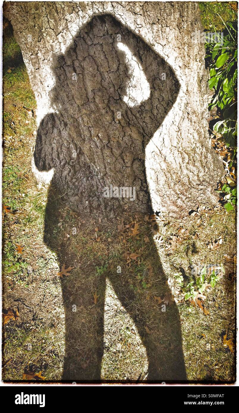 Shadow selfie holding hair back on a windy fall day - Stock Image