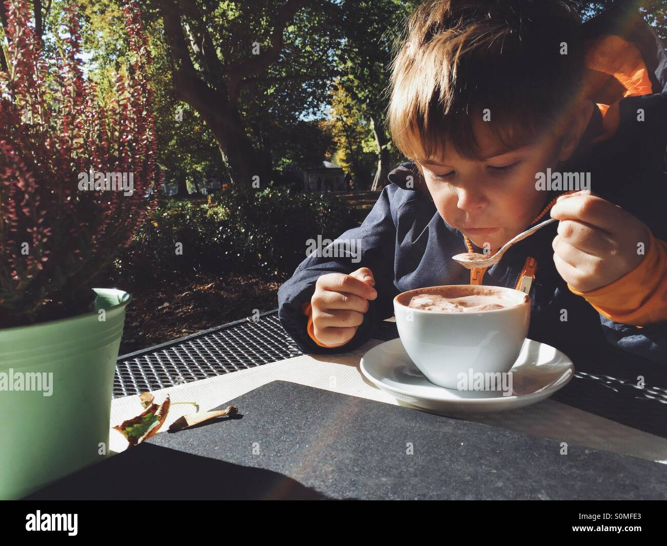 Five year old boy drinking hot chocolate outside - Stock Image