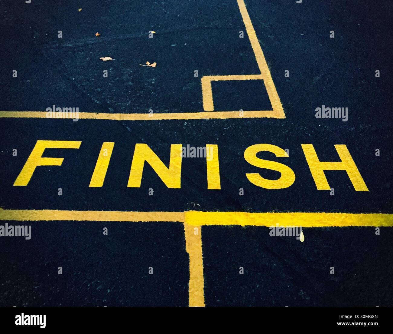 The word 'finish' painted in yellow on dark asphalt. - Stock Image