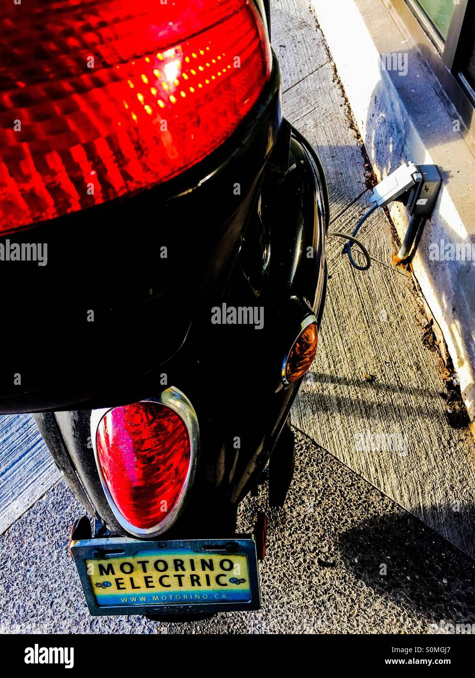 Electric motorcycle plugged in - Stock Image