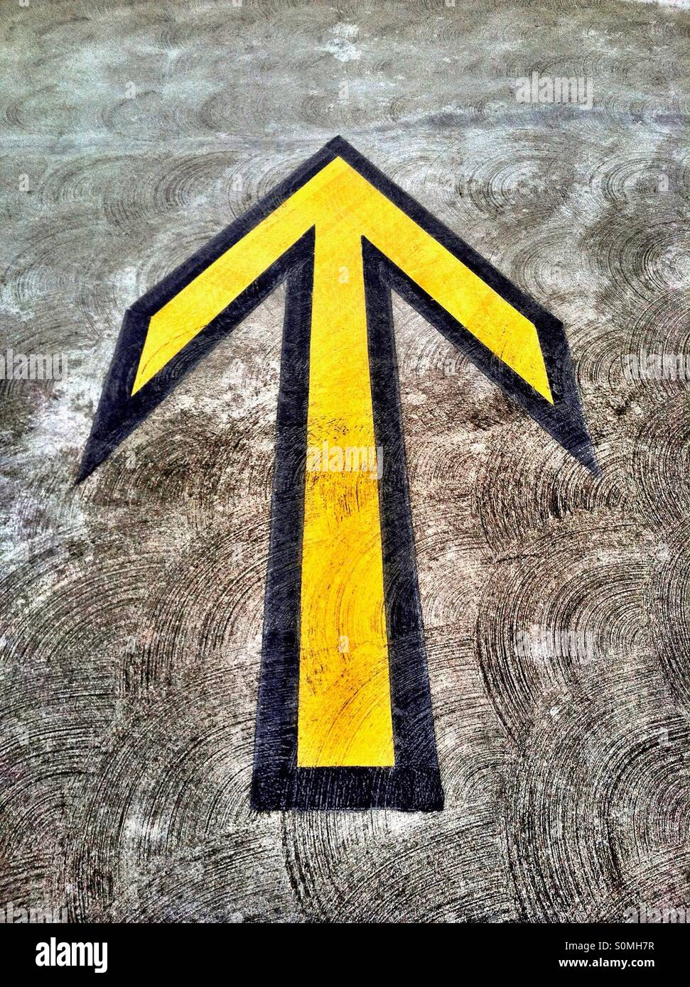 Yellow directional arrow on pavement in parking structure - Stock Image