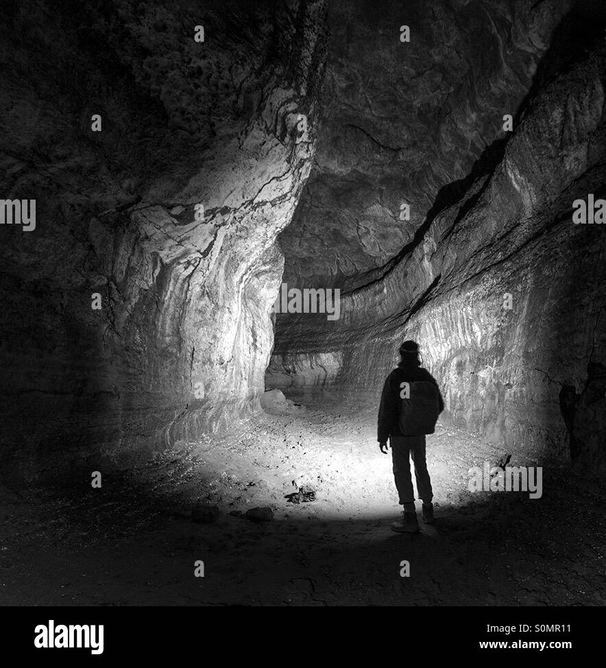 Silhouette of a man standing in lava tube - Stock Image