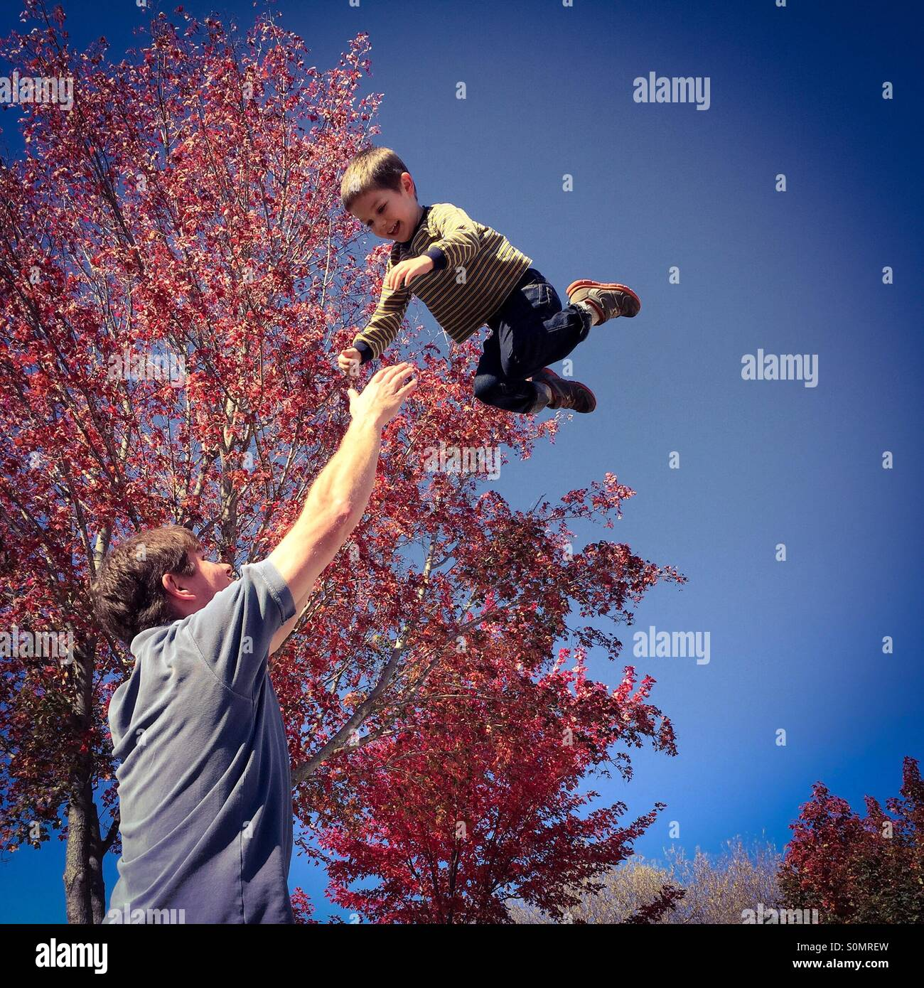 Image of a father tossing his laughing son into the air to catch him, taken during the autumn season - Stock Image