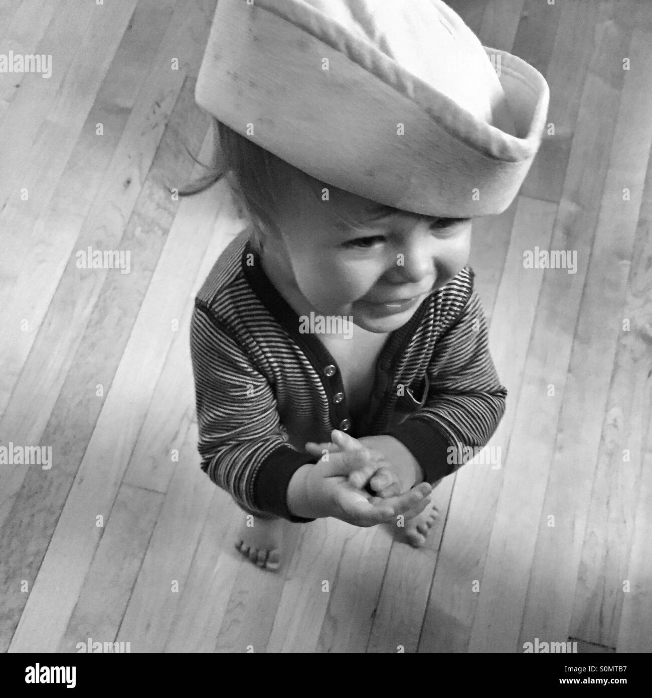 Black and white photo of a happy toddler wearing a uniform sailor's hat from the navy - Stock Image